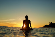 Surfer Sitting On Surfboard In Sea During Sunset