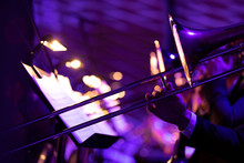 A Musician Playing A Trombone In A Big Band Trombone Section With Purple Stage Lights And Bright Warm Music Stand Lights