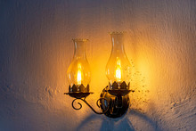Old Lamp Adapted For Electric Light On A Rustic And Wrinkled Wall