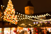 Winter Holidays And Celebration Concept - Blurred Christmas Market In Evening At Town Hall Square In Tallinn, Estonia