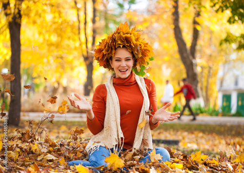 Young beautiful woman with a wreath of maple leaves posing in autumn park Fototapete