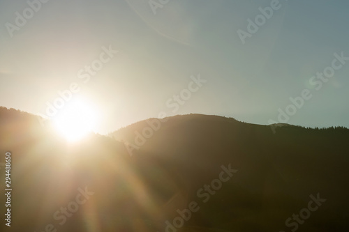 Sunny autumn mountain scene with sun ray