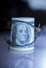 Economic Warfare, Sanctions And Embargo Busting Concept. US Dollar Wrapped In Barbed Wire.