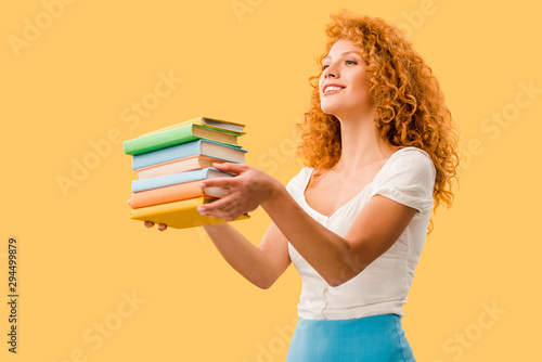 attractive smiling student holding books isolated on yellow