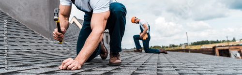 panoramic shot of handyman holding hammer while repairing roof near coworker - 294507864