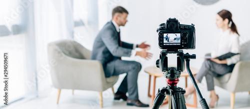 Fotomural selective focus of digital camera shooting journalist and businessman