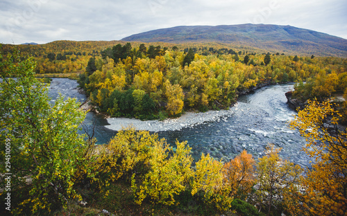Sunny fall autumn view of Abisko National Park, Kiruna Municipality, Lapland, Norrbotten County, Sweden, with Abiskojokk river, road and Nuolja mountain, near border of Finland, Sweden and Norway