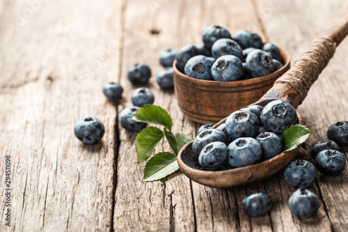 Blueberries in wooden spoon on old wood table. Healthy eating and nutrition concept. - 294511098