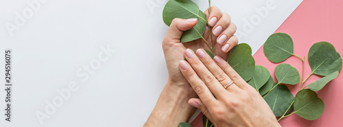Poster Manicure Stylish trendy female pink manicure. Beautiful young woman hands on pink pastel background with flowers and place for text. Minimal creative concept. Flat lay, top view, mock up, copy space, template