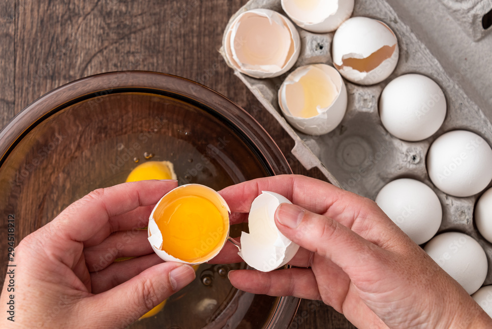 Fototapety, obrazy: Eggs in cardboard egg carton, woman's hands opening egg into glass bowl, raw egg in bowl, on a wood table