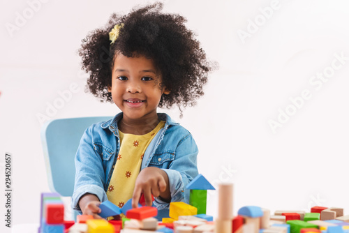Little afro girl smiling and playing colorful wooden toys. Fototapet