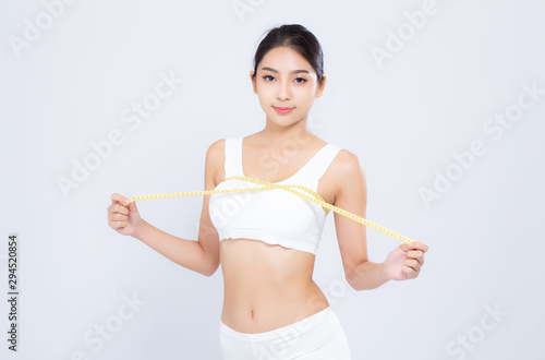 Beautiful portrait asian woman diet and slim with measuring breast and augmentation isolated on white background, girl have cellulite loss with tape measure, health and wellness concept Wallpaper Mural