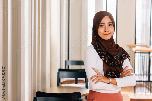 Fotografía  Young happy and successful South East Asian Islamic business woman with arms crossed in business corporate building setting looks at camera