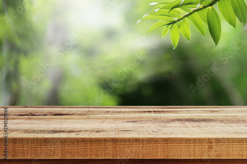 Wooden desk and green leaf nature in garden background.