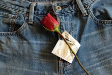 Condom And Red Rose And  Jeans On Valentine Day. Safe Sex, Love Of Sex Concept.