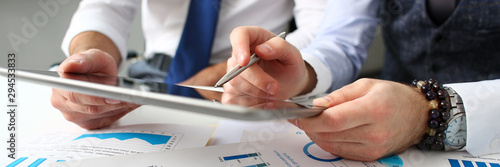 Group of businessmen point finger and silver pen in arms using electronic pad pc closeup Canvas Print