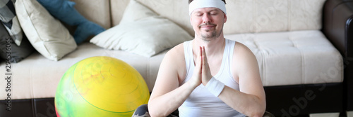 Valokuva  Male relaxing human body traning yoga aganist home background