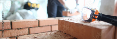 Focus on construction site made of red bricks and concrete. Professional engineer stacking special equipment and tools to properly fulfill construction. Building concept