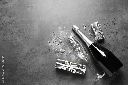 Cadres-photo bureau Fleur Flat lay composition with bottle of champagne for celebration on grey stone background. Space for text