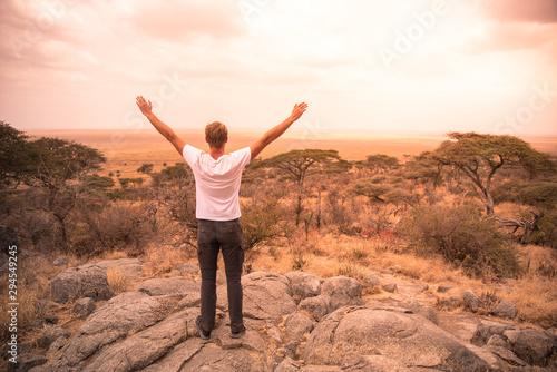 Fotografia, Obraz Man at view point looking to the bush savannah of Serengeti at sunset, Tanzania