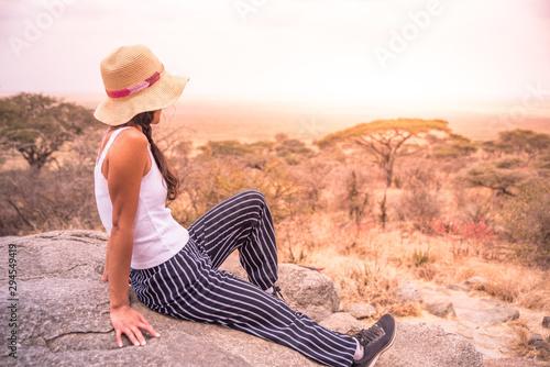 fototapeta na lodówkę Girl at view point looking to the bush savannah of Serengeti at sunset, Tanzania - Safari in Africa