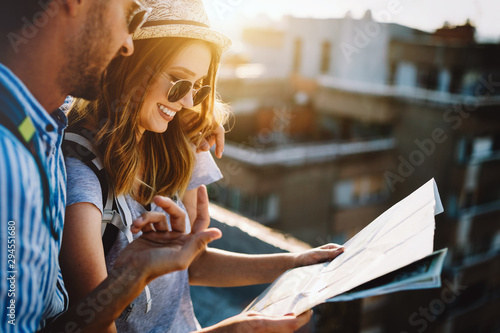 Multiethnic traveler couple using map together on sunny day - fototapety na wymiar