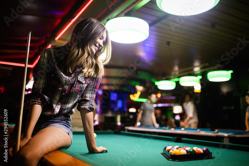 Canvas Young beautiful woman having fun and playing billiard in a club