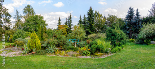 Tela Beautiful fall garden, with evergreen conifer trees