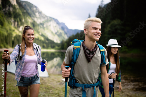 Fototapeta Trekking, camping, hiking and wild life concept. Group of friends are hiking in nature obraz na płótnie