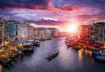FototapetaRomantischer Sonnenuntergang hinter dem Kanal Grande in Venedig, Italien, mit vorbeifahrender Gondel