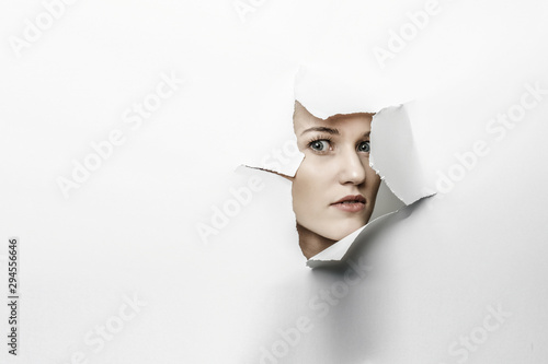 Fotomural Woman looking out from a hole of torn paper