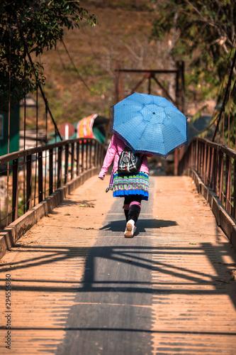 Fényképezés Hmong minority hilltribe woman in traditional costume with umbrella walking away