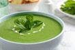 Leinwandbild Motiv Bowl of healthy green soup with fresh spinach on marble table, closeup view