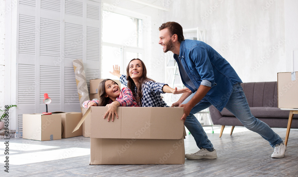 Fototapety, obrazy: Sheer euphoria. A perfect family of three people enjoying their time playing together after house moving and riding in a big cardboard box in the spacious living room.