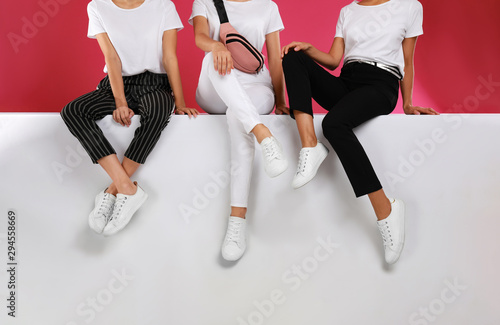 Women wearing stylish shoes on color background, closeup - 294558669