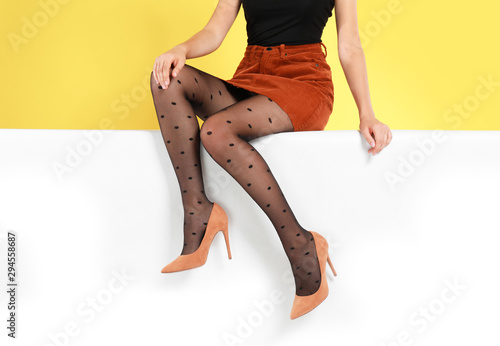 Poster Hoogte schaal Woman wearing stylish shoes on color background, closeup
