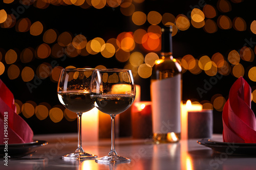 Romantic table setting with glasses of wine and burning candles against blurred Canvas Print