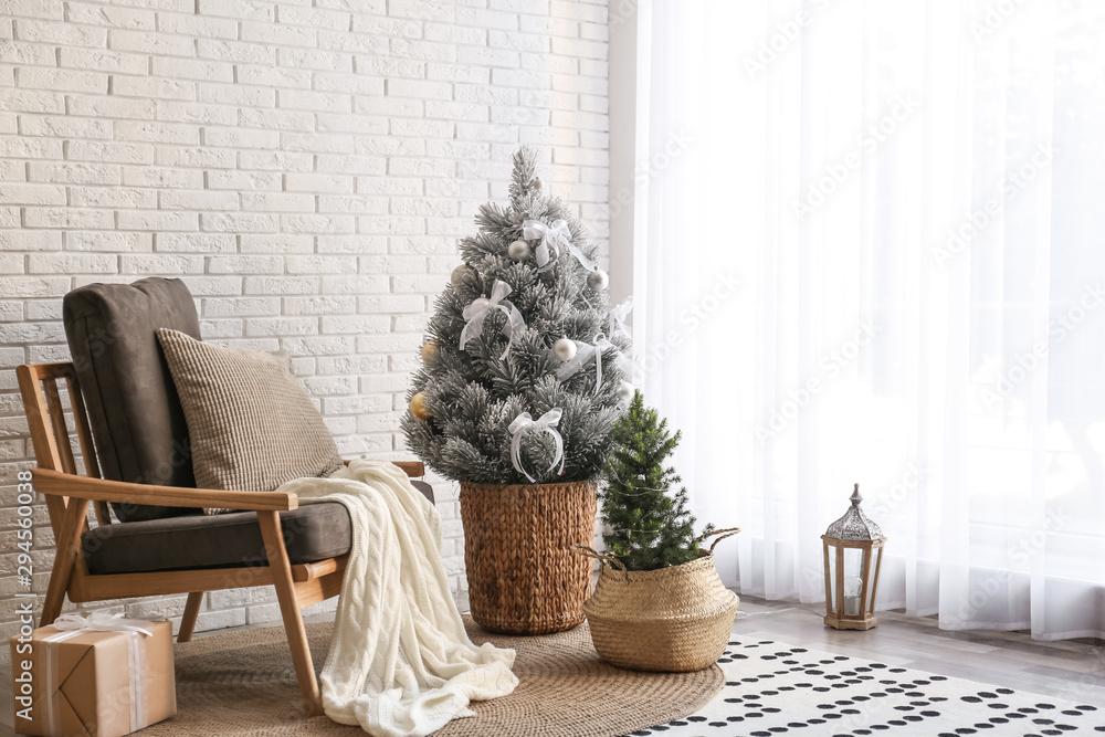Fototapeta Stylish interior with beautiful Christmas tree near white brick wall. Space for text
