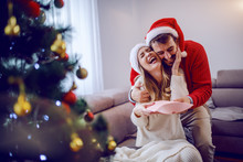Handsome Caucasian Man Giving Christmas Present To His Loving Girlfriend. Woman Hugging Man And Thanking Him For Gift. Both Are Dressed In Sweaters And Having Santa Hat On Heads. Christmas Holidays.