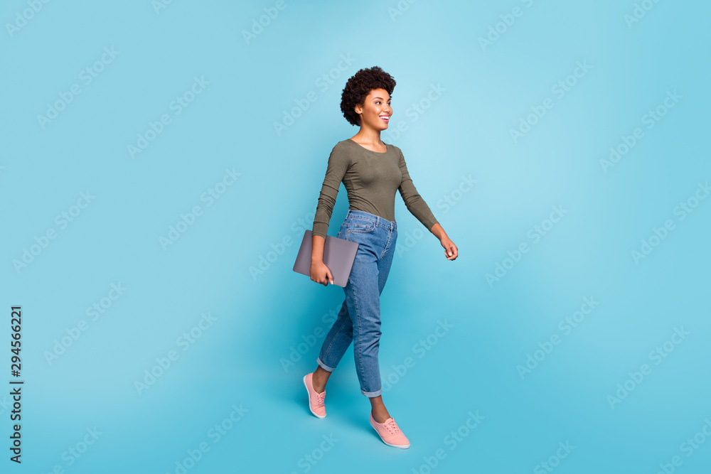 Fototapeta Full length photo of positive cheerful afro american girl hold her netbook go university for education learning wear casual style outfit denim jeans pink sneakers isolated blue color background