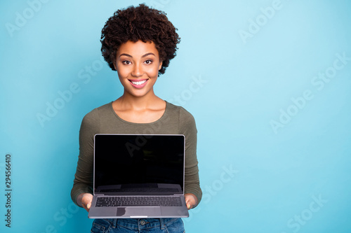 Photo of cheerful charming nice cute black woman demonstrating you new line of laptops with sales at once smiling toothily isolated over vivid color blue background - 294566410