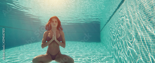 Young brunette woman in swimsuit do meditation on the depth of swimming pool, girl makes Namaste hands gesture symbol of yoga practice, healthy lifestyle body and mind health concept, horizontal view
