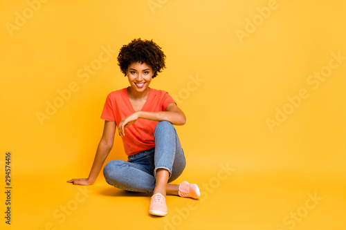 Portrait of positive charming cheerful girl sit have free time enjoy rest relax weekends wear casual style clothes sneakers isolated over yellow bright color background - 294574416