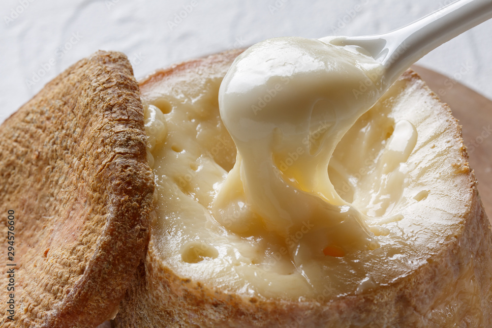 Fototapeta Spanish traditional sheep cheese with very creamy texture, almost liquid on white background.