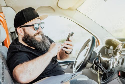Fotografie, Tablou  Urgent courier messenger checking his smart phone in his orange van