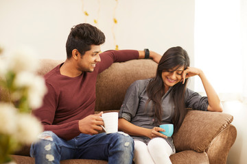 Cheerful young beautiful couple having coffee together on sofa at home.