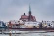 zimowy krajobraz Wrocławia stolicy Śląska, rzeka Odra wyjątkowo skuta lodem, widok na Ostrów Tumski z gotyckim kościołem Świętego Krzyża