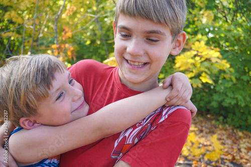 Photo The younger brother hugs the older one and looks at him, two loving brothers are standing in an embrace in the park against the background of autumn leaves