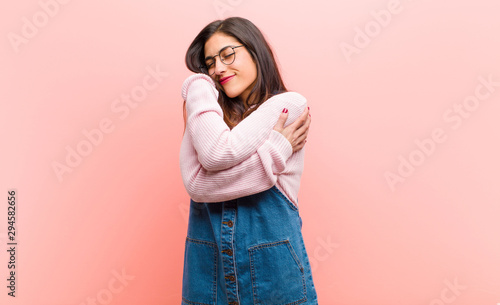 Fotografia young  pretty woman feeling in love, smiling, cuddling and hugging self, staying single, being selfish and egocentric against pink background