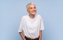 Teenager Girl With White Short Hair Over Blue Wall Laughing